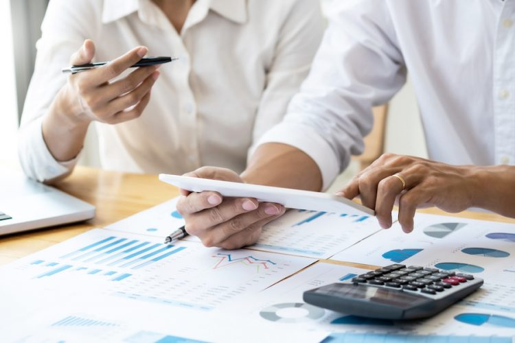 Two business teamwork calculating a valuation in workplace.