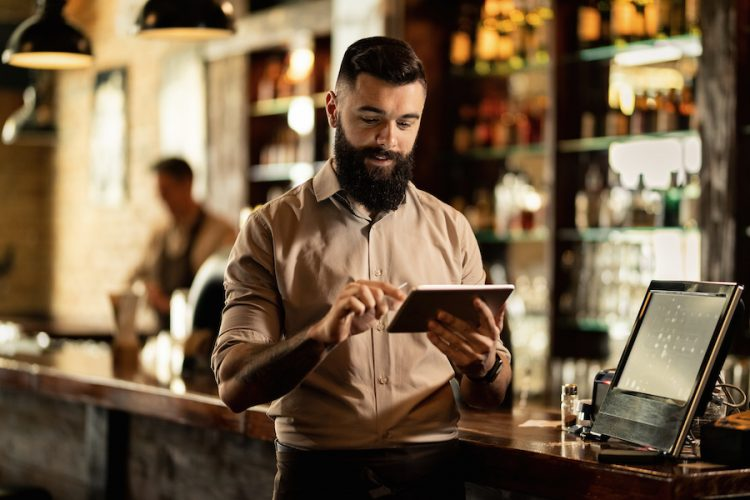 Young smiling waiter using touchpad while working in a pub.